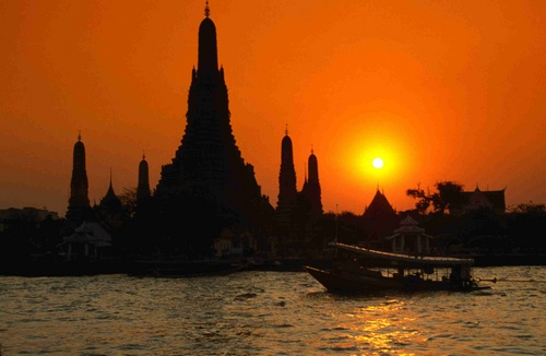 Sunset over the Temple of Dawn.  Wat Arun is silhouetted against the sky with the river Mae Nam Chao Phraya in the foreground