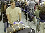 Passengers line up at the ticket counter at Miami International Airport in Miami, Friday, May 25, 2007. (AP)