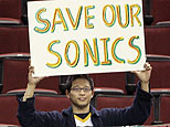 Seattle SuperSonics fan hold signs encouraging the team to remain in Seattle. (AP Photo/Elaine Thompson)