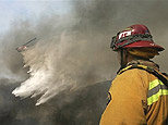 A firefighter watches as a helicopter makes a water drop ove a wildfire in Live Oak Canyon in eastern Orange County, Calif.  File from Wednesday, Oct. 24, 2007. (AP)